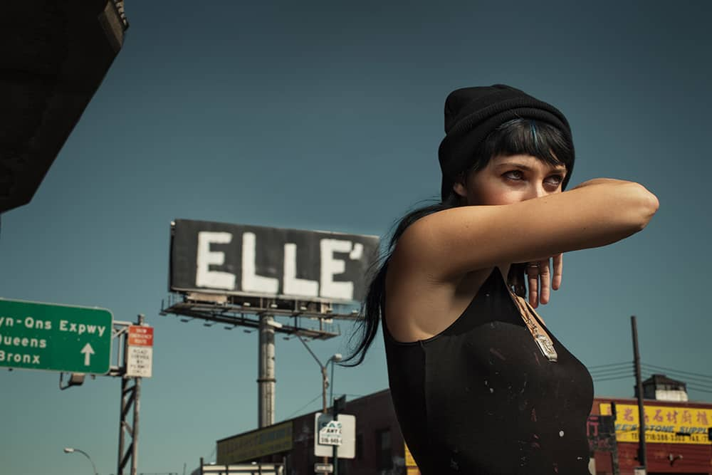 Portrait of the street artist ELLE She was photographed on a highway ramp, with a piece she had done above the Brooklyn – Queens Expressway in the background.
